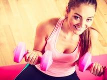 Mujer que levanta dos pesas de gimnasia Imagen de archivo libre de regalías