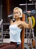 Mujer que levanta pesas de gimnasia pesadas Imagen de archivo