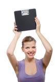 Mujer que levanta una escala del peso sobre su cabeza Imágenes de archivo libres de regalías