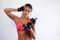 Mujer que levanta una pesa de gimnasia Foto de archivo