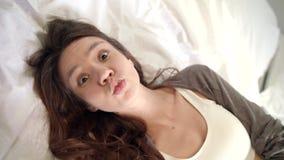 Mujer que liga con la cámara en cama Retrato de la muchacha feliz que se relaja en dormitorio almacen de metraje de vídeo