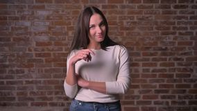 Mujer que liga con la cámara y que tuerce su pelo en el finger en para bricken el fondo metrajes