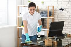 Mujer que limpia el escritorio de oficina de cristal imagen de archivo