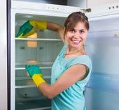 Mujer que limpia el refrigerador vacío Foto de archivo