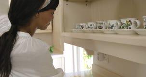 Mujer que limpia la cocina almacen de metraje de vídeo