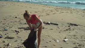 Mujer que limpia la playa almacen de metraje de vídeo