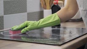 Mujer que limpia la superficie eléctrica de cerámica de cocinar moderna del vidrio almacen de metraje de vídeo