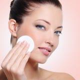 Mujer que limpia su cara con la esponja de algodón Imagen de archivo libre de regalías