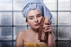 Mujer que limpia su cara con un cepillo de limpieza enorme Imágenes de archivo libres de regalías