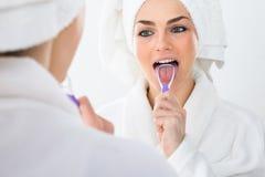 Mujer que limpia su lengua foto de archivo