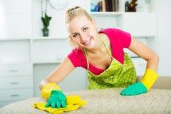 Mujer que limpia superficies dentro Fotos de archivo libres de regalías