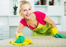 Mujer que limpia superficies dentro Imagen de archivo libre de regalías