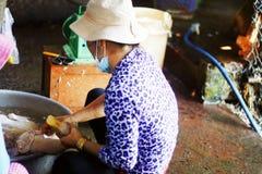 Mujer que limpia un pato para la venta Imagen de archivo libre de regalías