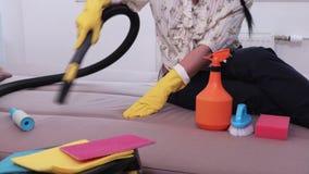 Mujer que limpia un sofá con un vacío metrajes