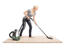 Mujer que limpia una alfombra con la aspiradora con el aspirador Fotografía de archivo libre de regalías