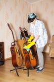Mujer que limpia una guitarra con un trapo Fotos de archivo