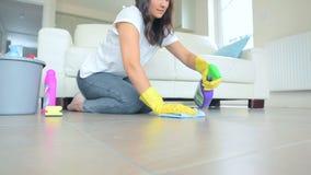 Mujer que limpia una sala de estar del piso metrajes