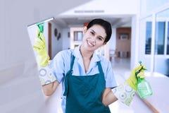 Mujer que limpia una ventana Fotografía de archivo libre de regalías