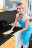 Mujer que limpia Worktop Imagenes de archivo