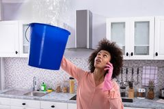 Mujer que llama al fontanero While Collecting Water del techo foto de archivo