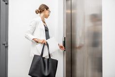 Mujer que llama el elevador foto de archivo
