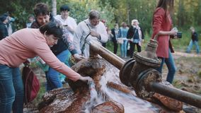 Mujer que llena encima de la botella de agua de waterspring en bosque, muchedumbre de gente almacen de video