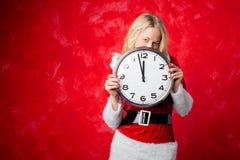 Mujer que lleva a cabo Año Nuevo que espera del reloj grande para Imagen de archivo