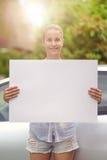 Mujer que lleva a cabo al tablero blanco vacío delante de su coche Imagen de archivo libre de regalías