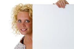 Mujer que lleva a cabo al tablero de mensajes blanco en blanco Imagenes de archivo