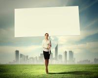 Mujer que lleva a cabo al tablero en blanco fotos de archivo libres de regalías