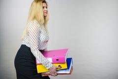 Mujer que lleva a cabo carpetas coloridas pesadas con los documentos Imagenes de archivo