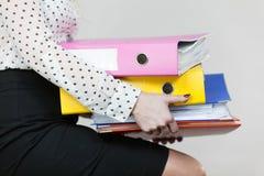 Mujer que lleva a cabo carpetas coloridas pesadas con los documentos Foto de archivo
