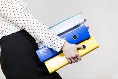 Mujer que lleva a cabo carpetas coloridas pesadas con los documentos Fotografía de archivo