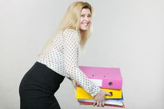 Mujer que lleva a cabo carpetas coloridas pesadas con los documentos Imágenes de archivo libres de regalías
