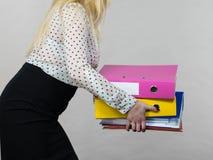 Mujer que lleva a cabo carpetas coloridas pesadas con los documentos Imagen de archivo libre de regalías