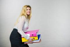 Mujer que lleva a cabo carpetas coloridas pesadas con los documentos Foto de archivo libre de regalías
