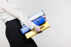 Mujer que lleva a cabo carpetas coloridas pesadas con los documentos Fotos de archivo libres de regalías
