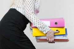 Mujer que lleva a cabo carpetas coloridas pesadas con los documentos Imagen de archivo