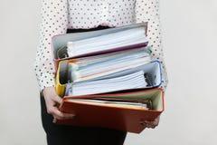 Mujer que lleva a cabo carpetas coloridas pesadas con los documentos Fotografía de archivo libre de regalías