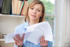 Mujer que lleva a cabo cuentas referidas sobre deuda fotos de archivo libres de regalías