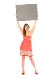Mujer que lleva a cabo el cartel en blanco Fotos de archivo
