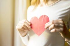 Mujer que lleva a cabo el corazón de papel rojo Concepto del día del amor y de tarjetas del día de San Valentín fotos de archivo libres de regalías