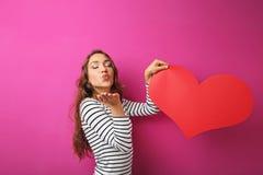 Mujer que lleva a cabo el corazón rojo Fotos de archivo libres de regalías