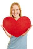 Mujer que lleva a cabo el corazón rojo como símbolo del amor Foto de archivo