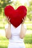 Mujer que lleva a cabo el corazón rojo grande antes de su cara Fotos de archivo