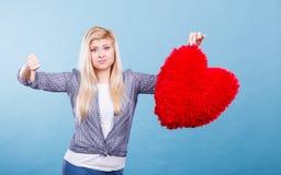 Mujer que lleva a cabo el corazón rojo que muestra el pulgar abajo Imagen de archivo libre de regalías