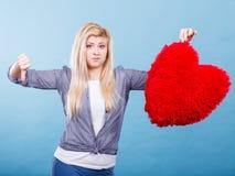Mujer que lleva a cabo el corazón rojo que muestra el pulgar abajo Imagenes de archivo