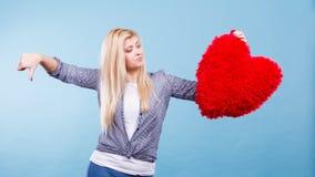 Mujer que lleva a cabo el corazón rojo que muestra el pulgar abajo Imágenes de archivo libres de regalías