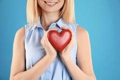 Mujer que lleva a cabo el coraz?n decorativo en fondo del color fotografía de archivo