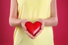 Mujer que lleva a cabo el coraz?n decorativo en fondo del color imágenes de archivo libres de regalías